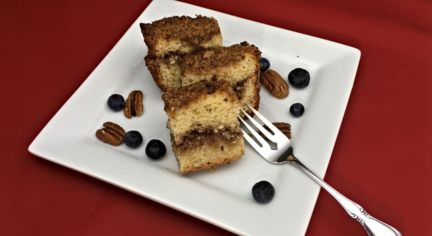 Coffeecake on a white plate with blueberries and pecans