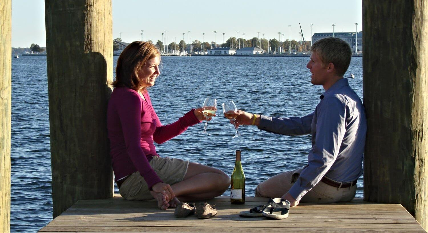Man and woman toasting with champagen glasses on a dock