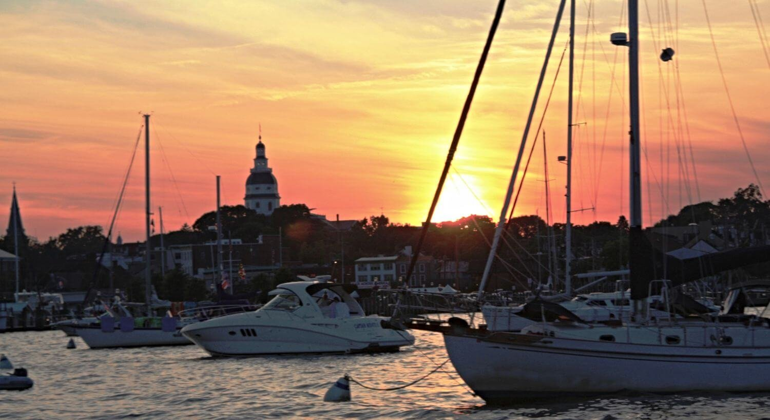Yachts and sailboats in the harbor at sunset
