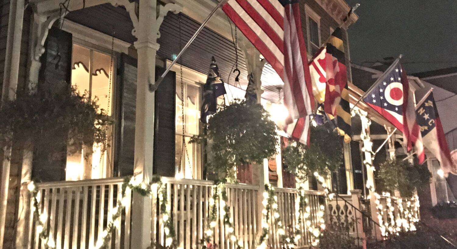 Lit-up flag flying from white-railed porch at night