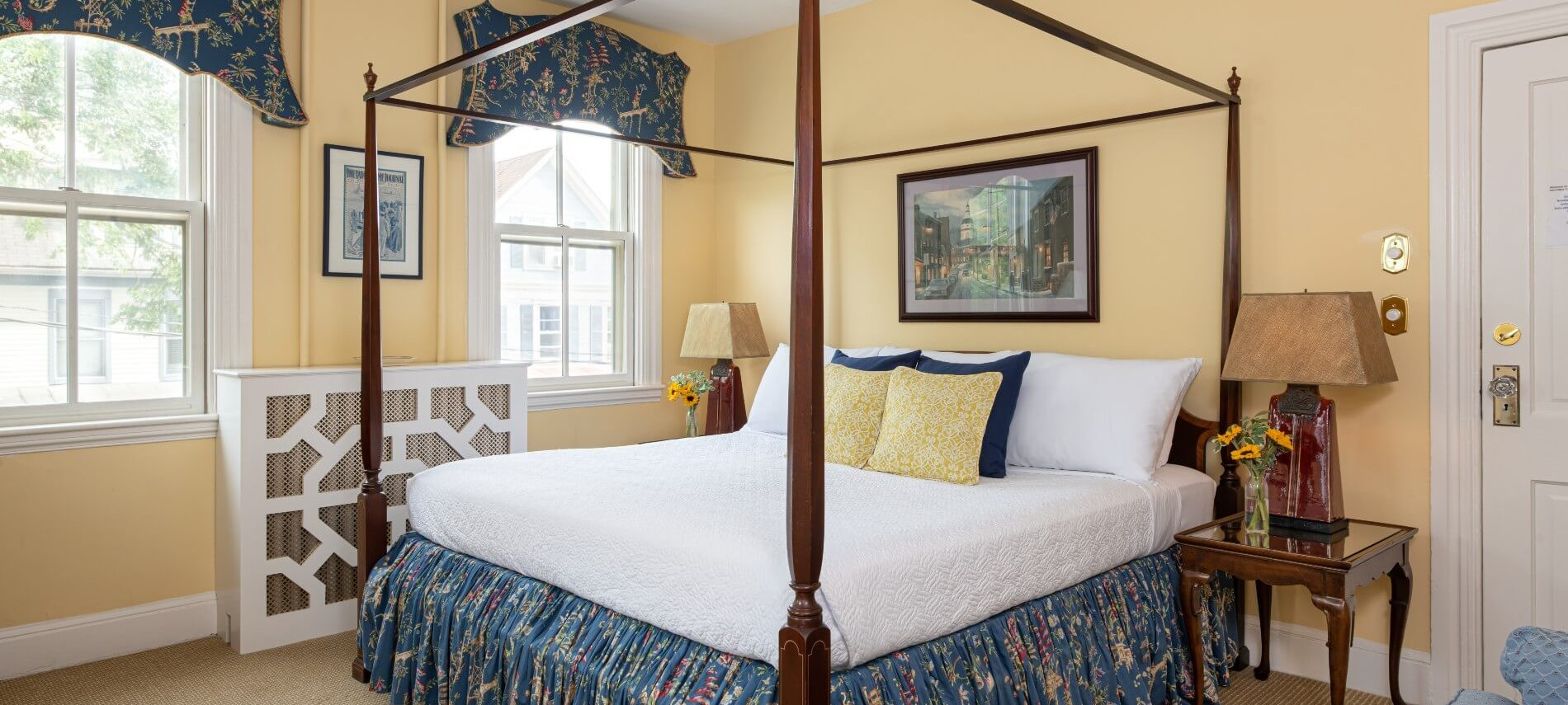 Large room with cream clored walls and a four poster bed with a blue coverlet