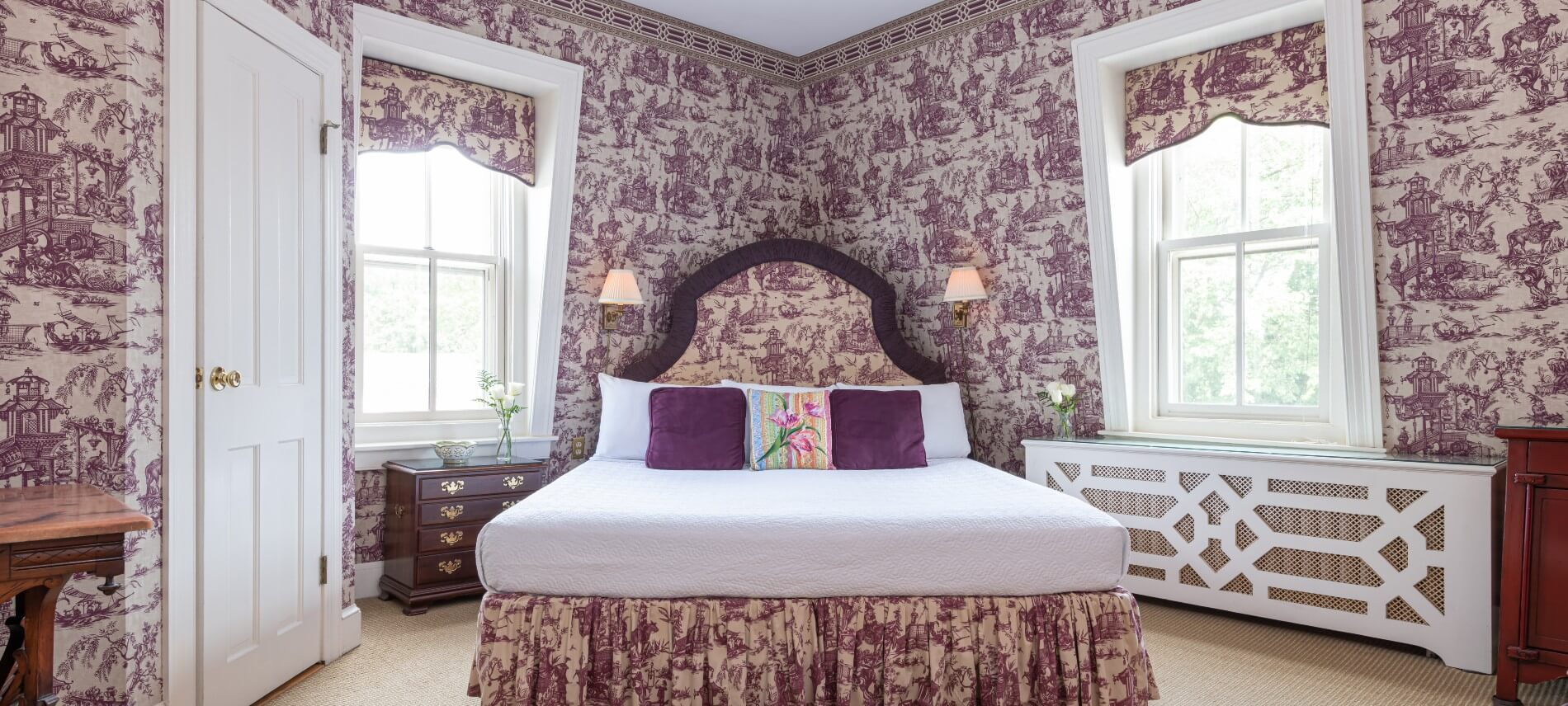 King sized bed with a purple coverlet in a lavishly wall-papered room