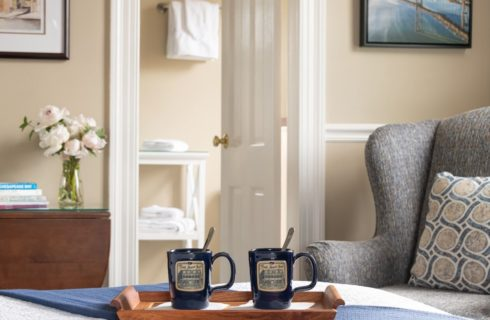 coffee cups on tray on bed, wing chair, bathroom