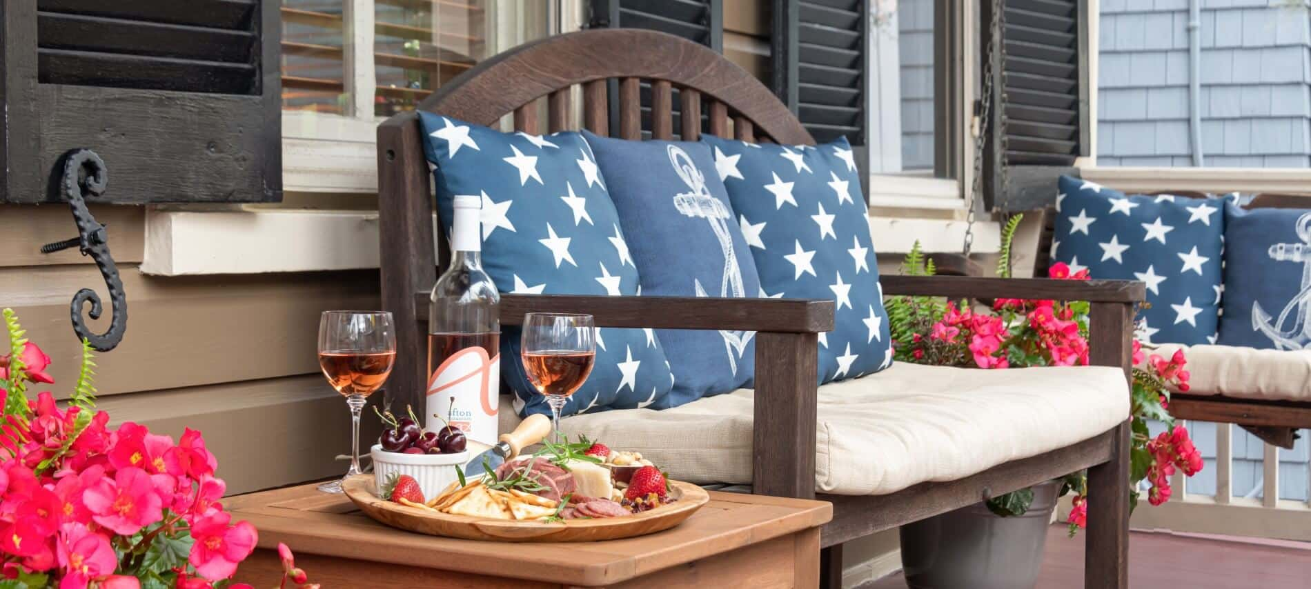 sitting bench with side table of food plate and glasses of wine