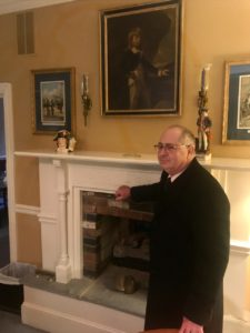 man standing by fireplace