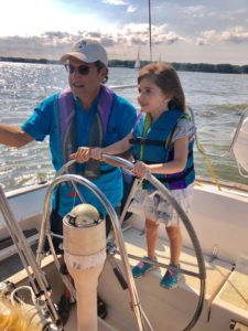 little girl steering a sailboat