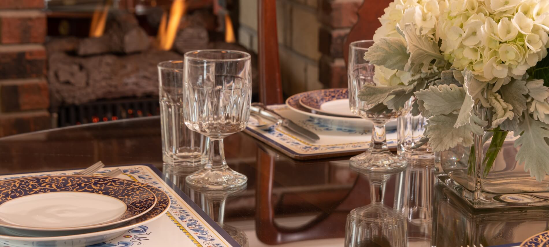 table set with place settings, fireplace in background