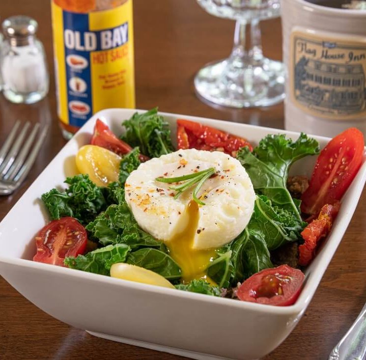 Breakfast with vegetables, poached egg, hot sauce, coffee cup