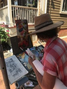 lady painting the Flag House Inn outdoors
