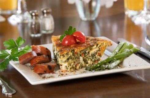 slice of vegetable quiche/pie, sausage slices, asparagus on a plate