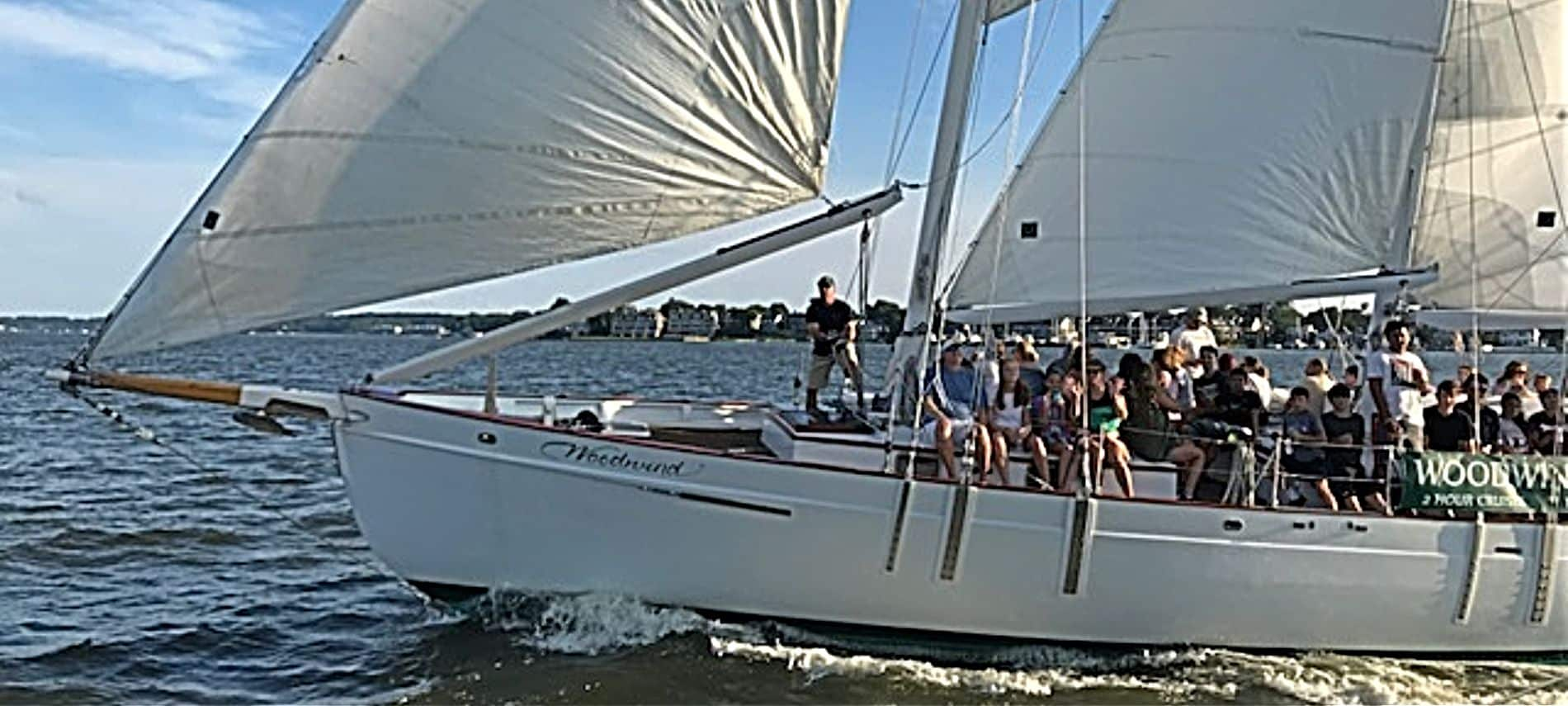 Group of people on large sail boat coating through the water