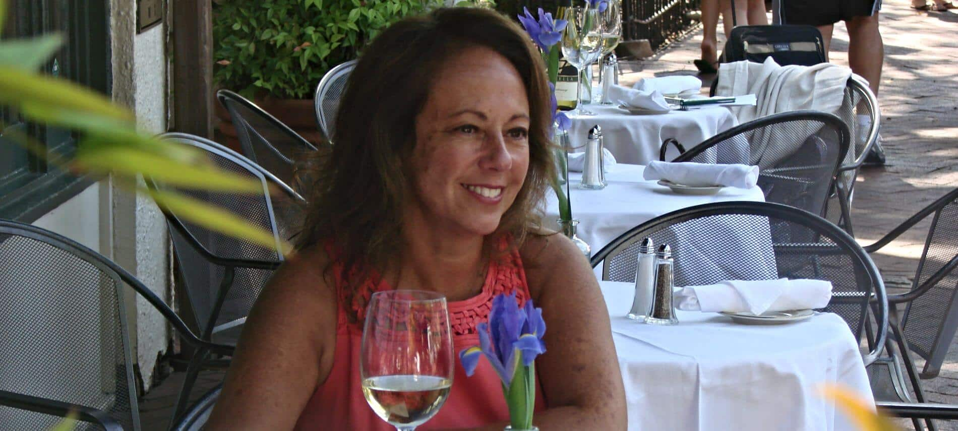 Smiling woman sitting at table outside with a glass of white wine