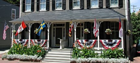 Front of Inn with flags flying from the porch
