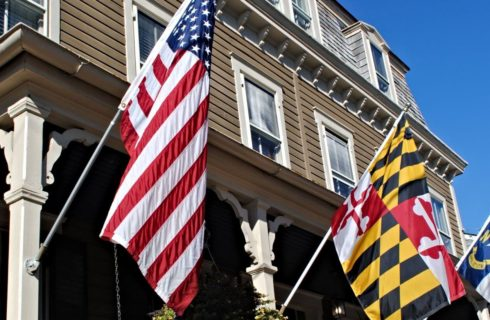 Flags flying from large white porch of a house with beige siding