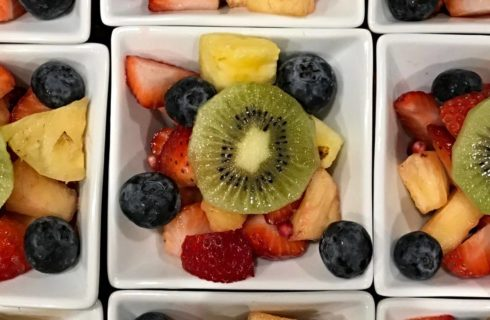 Colorful fruit cups with kiwi, berries, and pineapple