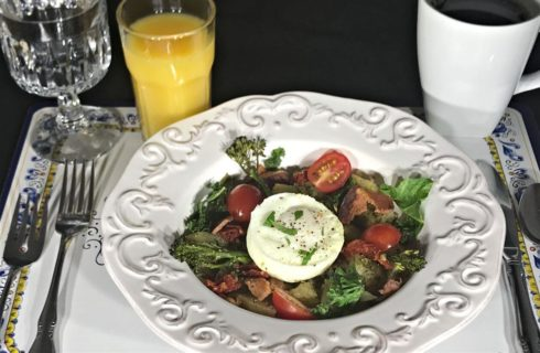 Poached egg on a bed of vegetables on an ornate white stonewear plate
