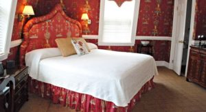 Large bed with white coverlet in room with ornate red wallpaper and padded headboard