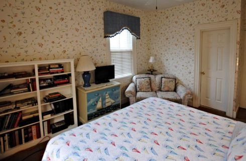 Large bright room with king bed and a reading area