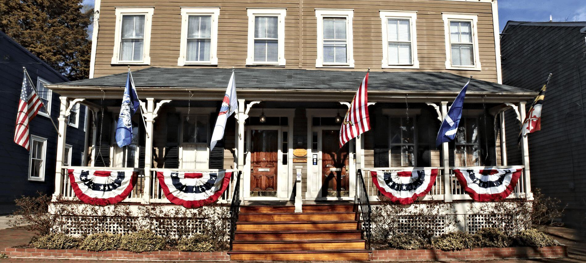 Large porch with wooden steps leading to bed and breakfast