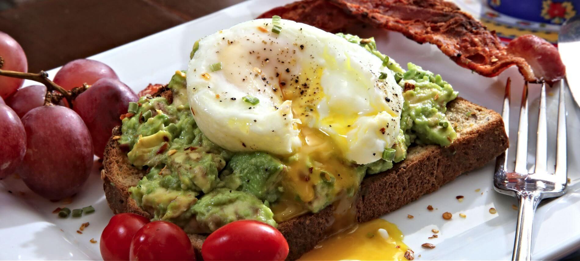 Avocado toast with a poached egg and bacon