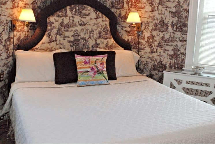 Beautiful large king bed with padded wooden headboard and a white coverlet