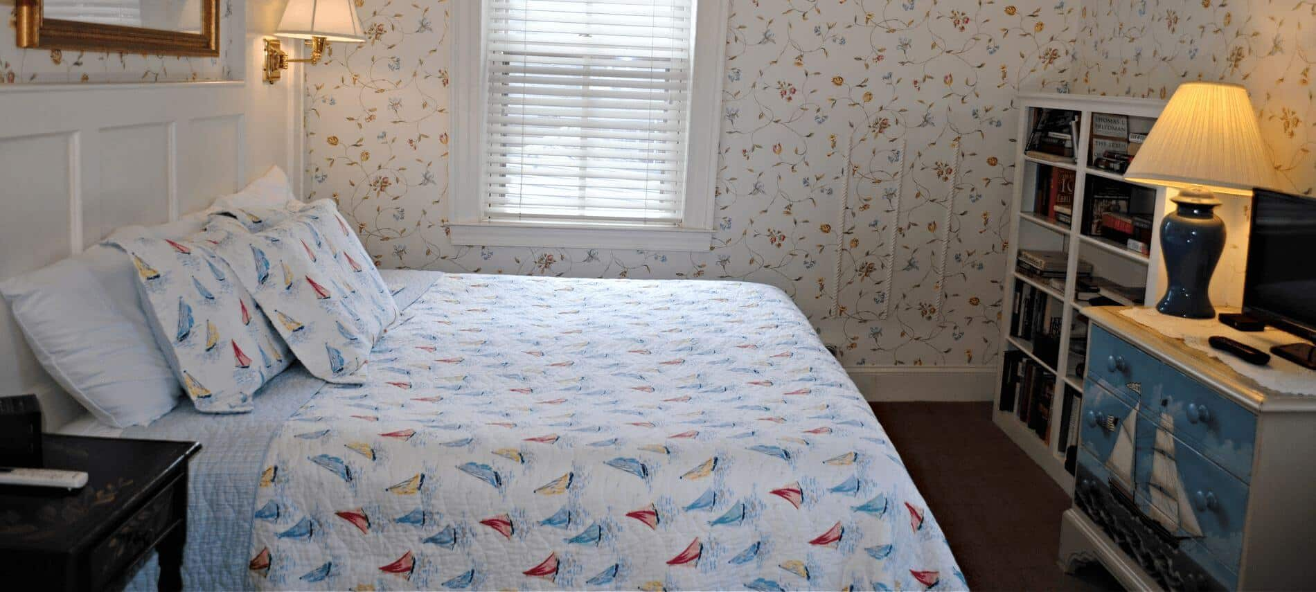 Large airy bright room with king sized bed with sailing motif