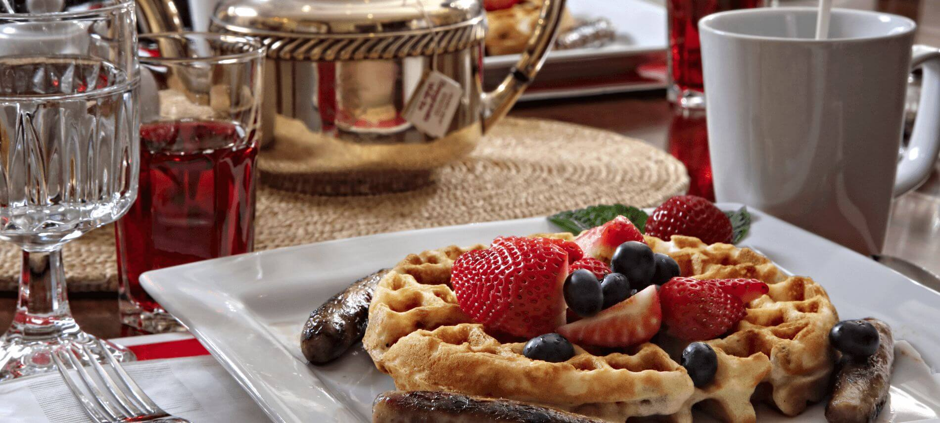 Waffles with fruit on a white plate next to a silver tea pot