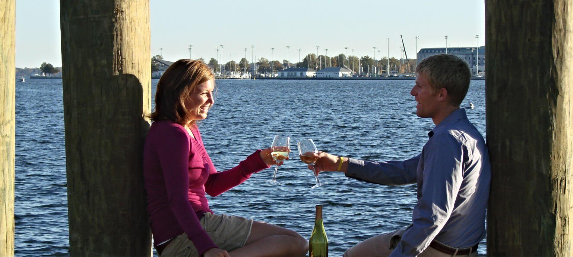Man and woman toasting with wine glasses on wooden dock