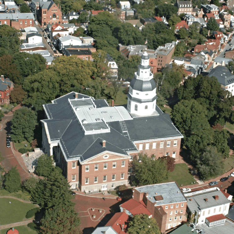 Arial view of large brick building surrounded by trees and buildings