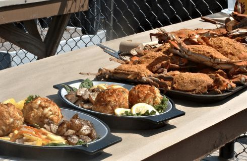 Platters of fried seafood on a wooden trestle table