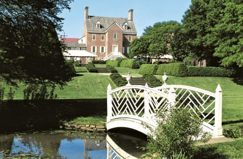Large brick manor house viewed from across white footbridge