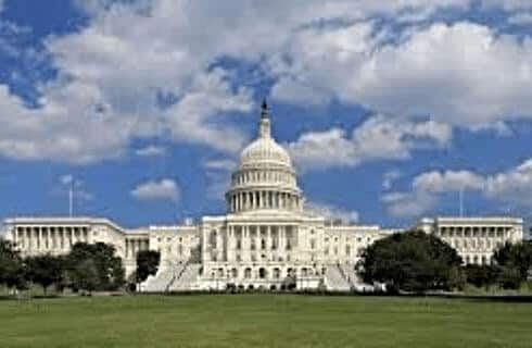 Large white capitol building on a grassy knoll