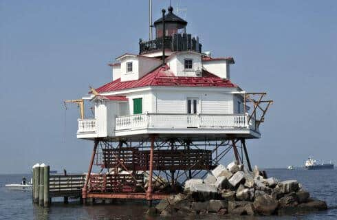 Large white lighthouse with red roof on stilts over water