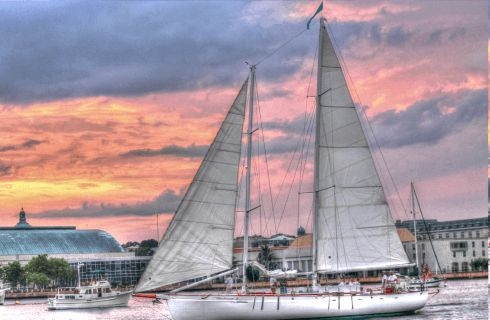 Large white sailboat in the harbor at sunset