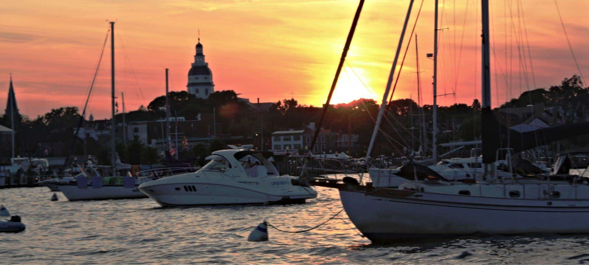 White yachts floating in harbor at sunset